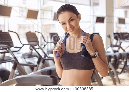 Young female training in gym healthy lifestyle holding skipping rope