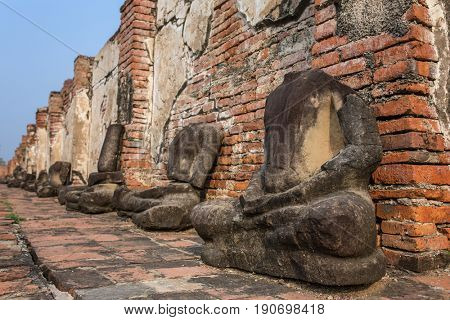 Detail of many headless Buddhas along a temple wall at Wat Mahathat, Temple of the Great Relic, in Ayutthaya, Thailand