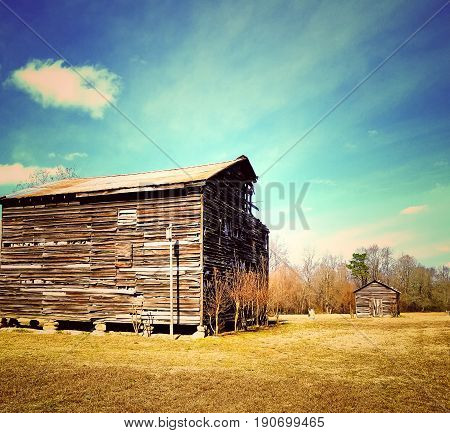 A large old wood barn and a smaller one in the background. Color filtered.