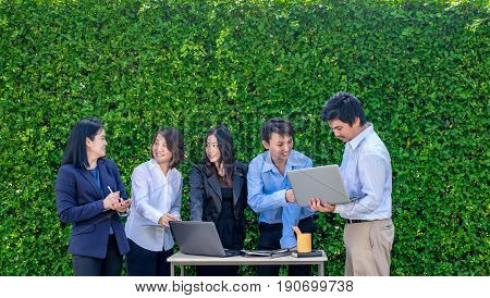 Businesswoman and businessman meeting outside office using laptop computer mobile phone and tablet device at green leaf wallmobile office concept.