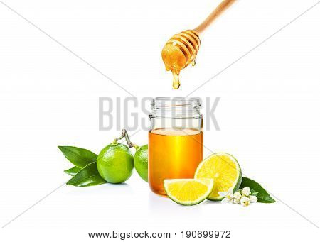 honey in glass jar honey dipper and cut fresh lime on isolated white bacground room for adding text or copy space