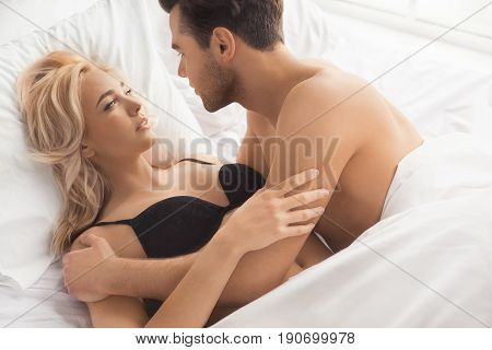 Young couple man and woman intimate relationship on bed covered with blanket passion