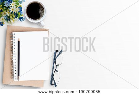 White minimal office desk table with notebookglassespenciland cup of coffee. Top view with copy space for text or picture flat lay.