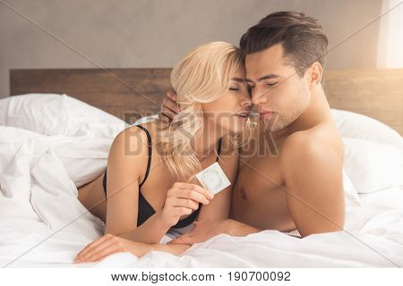 Young couple man and woman intimate relationship on bed holding condom