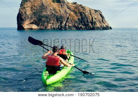Two people - an adult and a child father and son in life jackets sail on inflatable boats during hike at summer