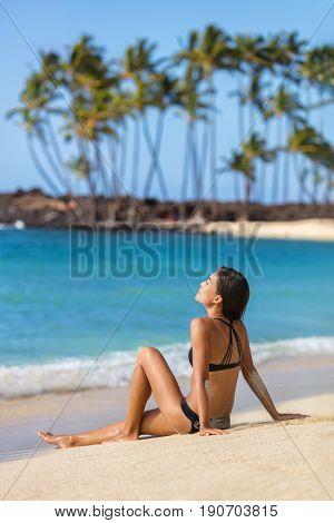 Exotic hawaii beach woman sunbathing relaxing on sand at tropical holiday destination. Hawaiian vacations under the sun. Asian girl in black bikini serene and peaceful.