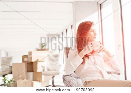 Thoughtful young businesswoman having coffee on chair in new office