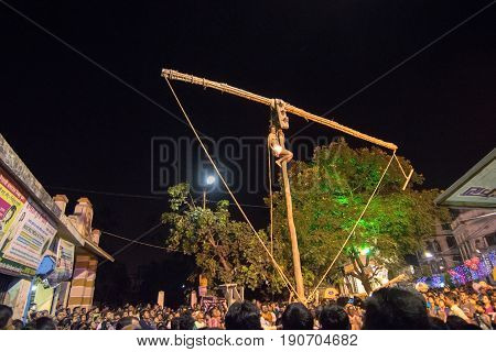 KOLKATA WEST BENGAL INDIA - 15 APRIL 2017: One Hindu devotee is hanging from pole in air at night. Religious sports for festival called