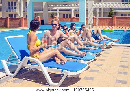 Party at smimming pool. Young friends in swimwear and sun glasses are drinking cocktails while sunbathing on the chaise longue near the pool. Cheers.