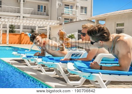 Cheers. Party at smimming pool. Young friends in swimwear and sun glasses are drinking beer while sunbathing on the chaise longue near the pool. They clink glasses