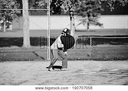 A teenage boy umpiring a baseball game in casual clothes and a chest protecter and a face mask in black and white