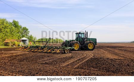 A tractor with attached cultivator working the land in a rural summer countryside landscape
