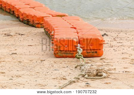 Close up end of orange sea buoys tied on sea beach marine equipment for marking safety zone.