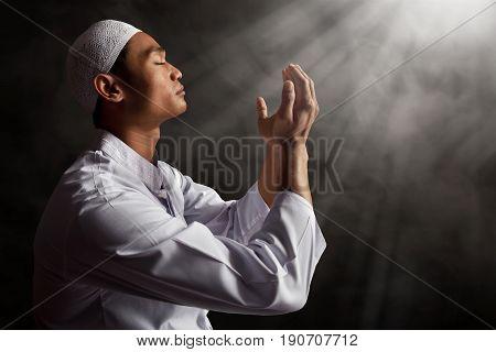 Asian muslim man praying to god on smoke background