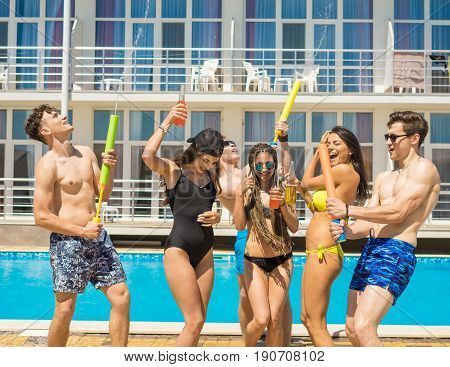 Party at smimming pool. Group of cheerful friends drinking cocktails and beer dancing and jumping at the pool. Guys shoot water pistols