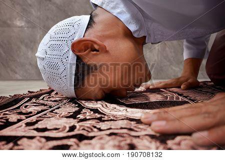 Muslim man praying to god in mosque