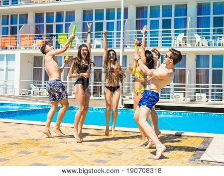 Party at smimming pool. Group of cheerful friends drinking cocktails and beer dancing and jumping at the pool. Guys shoot water pistols. Moment of dancing