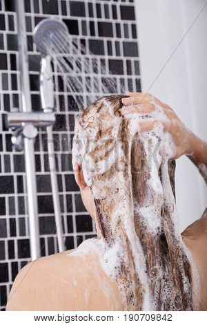 Woman Washing Head And Hair In The Shower By Shampoo, Rear View