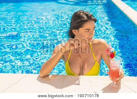 portrait of young sexy girl at swimming pool, wearing bikini. She is putting off sunglasses and looking for somebody. drinking red cocktail during vacation. Pool party