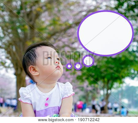cute baby girl think something in garden concept
