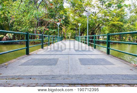 cement bridge over pond with metal handrails on park
