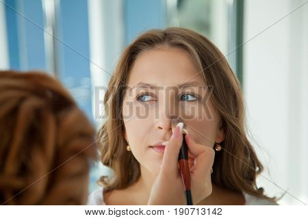 Make-up artist applying bright base color eyeshadow on model's eye , close up