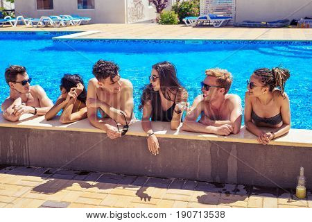 Party at smimming pool. Group of cheerful friends at the edge of the swimming pool drinking cocktails and talking and smiling