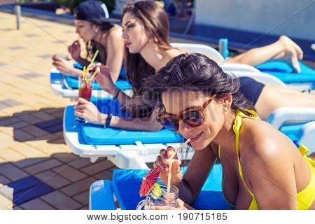 Three Beautiful girls in swimwear and sun glasses are drinking cocktails through a straw while sunbathing on the chaise longue near the pool.