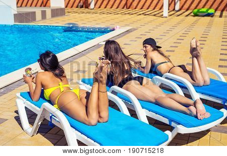 Three sexy girls in swimwear and sun glasses are drinking cocktails through a straw while sunbathing on the chaise longue near the pool.