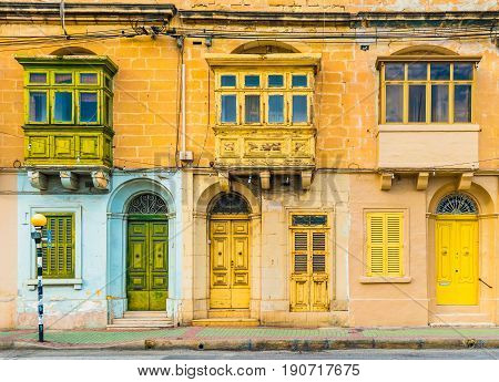 Malta Valletta: Facade of a residential house with traditional maltese balconies. House made of yellow bricks in the street of Malta.