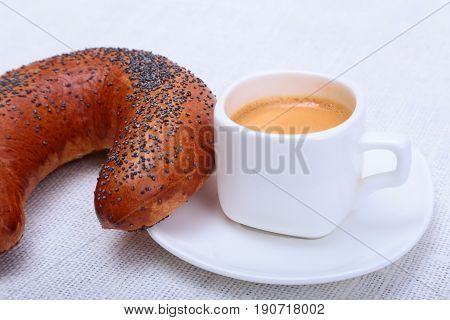 Fresh homemade bagel, muffin, cake and white cup of Cappuccino on white background