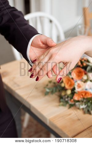 wedding rings and hands of bride and groom. young wedding couple at ceremony. matrimony. man and woman in love. two happy people celebrating becoming family.