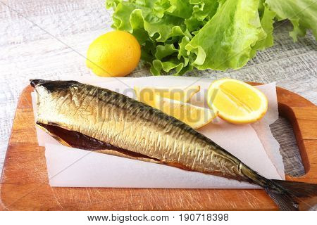 Smoked mackerele and lemon on green lettuce leaves on Wooden cutting board isolated on white background