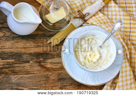 Sweet milk pasta in white bowl on plate towel butter dish spaghetti on wooden table