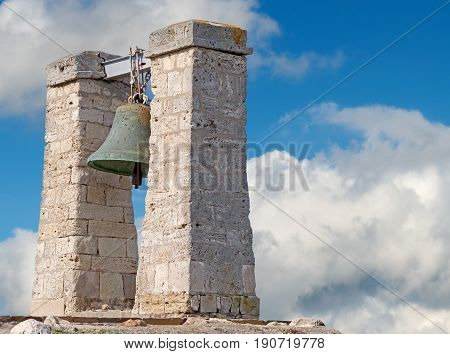 Bell from Notre Dame de Paris on background of blue sky. Now situated in Chersonese