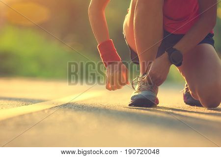 Young fitness woman runner tying shoelace before run on morning tropical forest trail