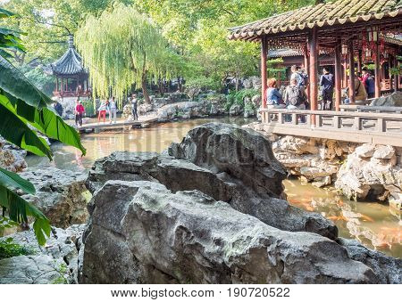 Shanghai, China - Nov 4, 2016: In Yu Yuan (Yu Garden) - A tranquil traditional Chinese architectural scene; amid landscaped trees, rockery, pond and bush.