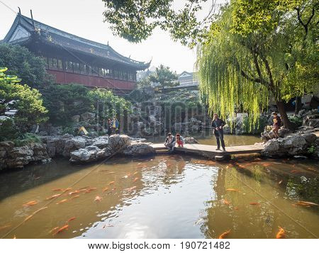 Shanghai, China - Nov 4, 2016: In Yu Yuan (Yu Garden) - A tranquil traditional Chinese architectural scene, featuring landscaped trees, rockery, pond and bush.