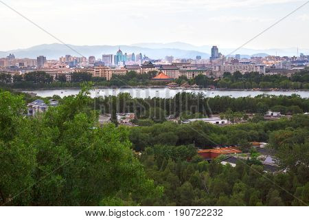 Cityscape of Beijing downtown from above, view on Northern Sea of Beihai Park in summer at the end of the day