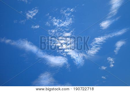 Light white cirrus clouds of beautiful shape on blue sky