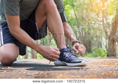 Cropped shot of young man runner tightening running shoe laces