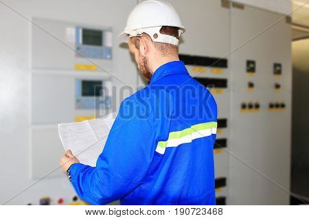 An electrician is looking at the electrical circuit on the blurred background of the control panels. Worker in white helmet reads the user manual near electrical equipment