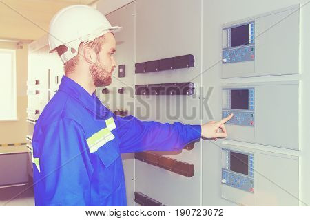 Engineer industrial complex runs the hardware test from the control panel. Engineer starts equipment with  remote control. Worker in white helmet presses on  control panel.
