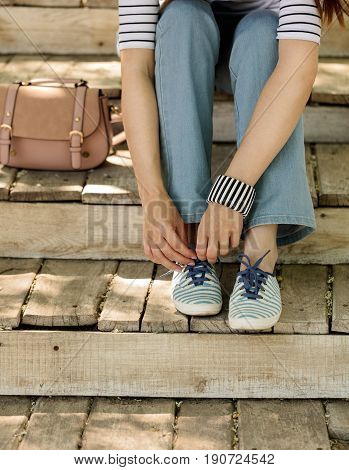 Young woman in blue jeans and striped sneakers sits on old wooden steps and ties up shoelaces. Selective focus.