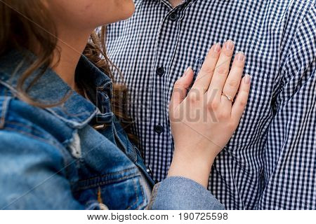 Hand of young woman with wedding ring on the chest of man in plaid shirt. Couple in love. Man and woman are standing embracing