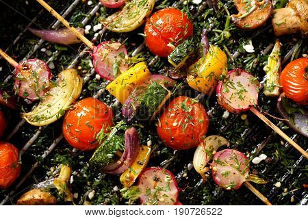 Grilled vegan skewers with cherry tomatoes, radishes, peppers and onions with fresh dill on a grill pan, top view