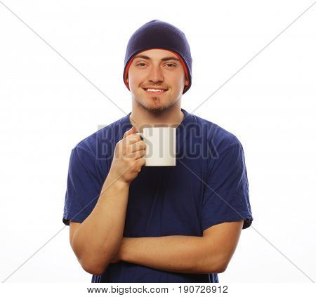 life style, food  and people concept: casual young man holding white cup with coffee or tea.