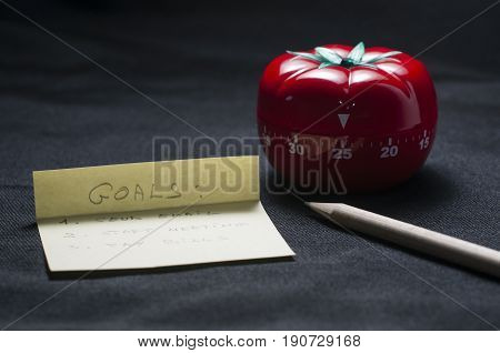 Mechanical Tomato shaped kitchen timer for cooking studying and working with pencil and goal list.