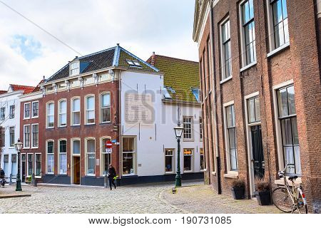 Leiden, Netherlands - April 7, 2016: Street view, traditional houses, poems on the wall and bicycles in Leiden, Holland, Netherlands