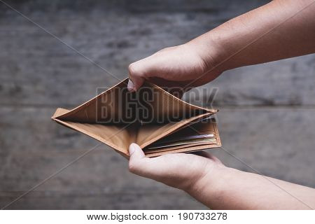 Hands opening empty wallet, no money concept
